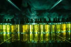 Vape-Konzept Rauchwolken und vape flüssige Flaschen auf dunklem Hintergrund Große Party und Leistung Lizenzfreie Stockbilder