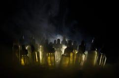 Vape-Konzept Rauchwolken und vape flüssige Flaschen auf dunklem Hintergrund Große Party und Leistung Stockbild