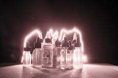 Vape-Konzept Rauchwolken und vape flüssige Flaschen auf dunklem Hintergrund Große Party und Leistung Stockfotografie
