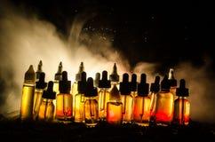 Vape-Konzept Rauchwolken und vape flüssige Flaschen auf dunklem Hintergrund Große Party und Leistung Lizenzfreie Stockfotografie