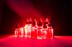 Vape-Konzept Rauchwolken und vape flüssige Flaschen auf dunklem Hintergrund Große Party und Leistung Lizenzfreie Stockfotos