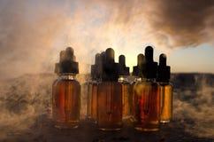 Vape-Konzept Rauchwolken und vape flüssige Flaschen zur Sonnenuntergangzeit blured Hintergrund Große Party und Leistung Nützlich  Stockfotos