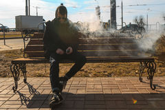 Vape man. A handsome young white guy in sunglasses and in the hood is sitting on the bench and smoking an electronic cigarette. Royalty Free Stock Photo