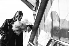 Vape man. A handsome young white guy in sunglasses and in the hood is standing and vaping an electronic cigarette. Black and white Royalty Free Stock Images