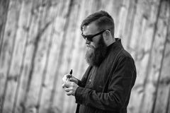 Vape man. Outdoor portrait of a young brutal white guy with large beard vaping electronic cigarette opposite the old wooden fence. Vape man. Outdoor portrait of stock photo