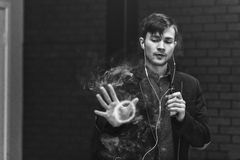 Vape man. Young handsome white guy let rings out of steam from electronic cigarette. Black and white photo. stock image
