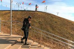 Vape-Mann Ein hübscher junger weißer Kerl in der Sonnenbrille geht die Treppe hinunter und raucht eine elektronische Zigarette Stockbild
