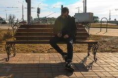 Vape-Mann Ein hübscher junger weißer Kerl in der Sonnenbrille und in der Haube sitzt auf der Bank und raucht eine elektronische Z Stockbild