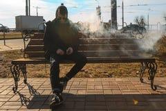 Vape-Mann Ein hübscher junger weißer Kerl in der Sonnenbrille und in der Haube sitzt auf der Bank und raucht eine elektronische Z Lizenzfreies Stockfoto