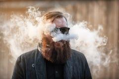 Vape-Mann Porträt im Freien eines jungen groben weißen Kerls mit dem großen Bart, der Hauche aus Dampf von einer elektronischen Z stockbild