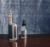 Vape przyrząda, papieros dla vaping, ciecz w butelce i telefon komórkowy przy s, Zdjęcia Stock