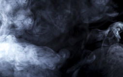 Vape Smoke on Black Background. Smoke from a Vape with light effects on a black background. The image is an abstract texture with copy or text space. It has royalty free stock photography