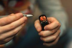 Vape sprzedaży usługa papieros Męskie ręki regulują elektroniczne papierosowe zwitki z pincette rozjarzona spirala zdjęcia royalty free