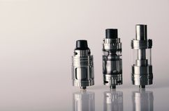 Vape tanks for electronic cigarette or e cig over a whi. Te background. vaping heads royalty free stock photos