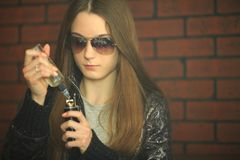 Vape teenager. Portrait of young cute girl in sunglasses smoking an electronic cigarette in the bar. Bad habit. Close up. Vape teenager. Portrait of young cute royalty free stock photos
