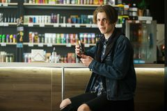 Vape teenager. Portrait of young handsome guy smoking an electronic cigarette in the vape bar. Bad habit that is harmful to health royalty free stock image