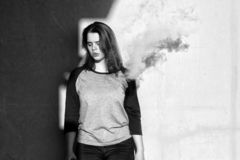 Vape teenager. Young cute girl in  casual clothes smokes an electronic cigarette near the wall outdoors in summer day. Bad habit. Vape teenager. Young cute girl stock photo