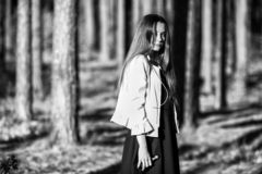 Vape teenager. Young cute girl in casual clothes smokes an electronic cigarette outdoors in the forest at sunset in summer. Bad habit that is harmful to health royalty free stock photography
