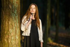 Vape teenager. Young cute girl in casual clothes smokes an electronic cigarette outdoors in the forest at sunset in summer. Bad habit that is harmful to health royalty free stock photo