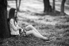 Vape teenager. Young cute girl in a dress sits near a tree and smokes an electronic cigarette outdoors in a park in spring. Bad. Habit that is harmful to health royalty free stock images