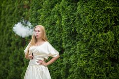 A young cute white girl in a dress is vaping an electronic cigarette on the street in summer. Vape teenager. A young cute white girl in a dress is vaping an royalty free stock image
