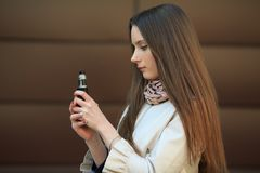 Vape teenager. Young white girl in casual clothing smoking an electronic cigarette opposite modern brown background on the street. Vape teenager. Young pretty royalty free stock photos