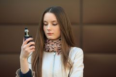 Vape teenager. Young white girl in casual clothing smoking an electronic cigarette opposite modern brown background on the street. Vape teenager. Young pretty stock photos