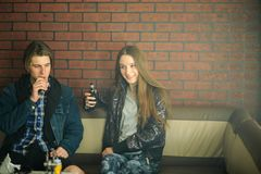 Vape teenagers. Young cute girl and young handsome guy smoke an electronic cigarettes in the vape bar. Bad habit. That is harmful to health. Vaping activity stock images