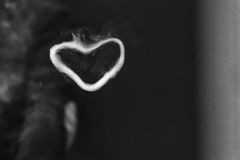 Vape trick. Ring out of steam in the shape of a heart from e-cigarette for background. Vaping. Black and white. Royalty Free Stock Photos