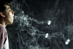 Vape trick rings in performance of vaper on dark background.  royalty free stock photography