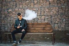 Vape Un individuo hermoso joven se sienta en el banco y sopla el vapor de un cigarrillo electrónico Foto de archivo libre de regalías