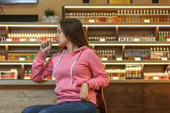 Vape woman. Young cute girl in pink hoodie smoking an electronic cigarette. Vape woman. Portrait of young cute girl in pink hoodie smoking an electronic stock image