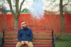Vape. Young brutal man with large beard and fashionable haircut in sunglasses smokes an electronic cigarette on the red bench. Royalty Free Stock Images