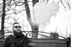 Vape. Young brutal man with large beard and fashionable haircut in sunglasses smokes an electronic cigarette on the red bench. Vape. Young brutal man with large Royalty Free Stock Image
