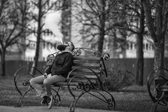 Vape. Young brutal man with large beard and fashionable haircut in sunglasses smokes an electronic cigarette on the red bench. Vape. Young brutal man with large Royalty Free Stock Photo