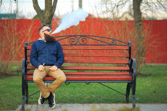 Vape. Young brutal man with large beard and fashionable haircut in sunglasses smokes an electronic cigarette on the red bench. Vape. Young brutal man with large stock photography