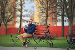 Vape. Young brutal man with large beard and fashionable haircut in sunglasses smokes an electronic cigarette on the red bench in t Stock Photos