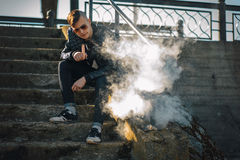 Vape. A young handsome guy sits on the stairs and blows steam from an electronic cigarette. Stock Photos