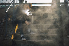 Vape. A young handsome guy sits on the stairs and blows steam from an electronic cigarette. Royalty Free Stock Image