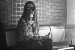 Free Vape. Young Handsome White Girl In Sunglasses Is Admiting Puffs Of Steam From The Electronic Cigarette. Teenager. Black And White. Stock Images - 93502994