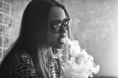 Vape. Young handsome white girl in sunglasses is admiting puffs of steam from the electronic cigarette. Teenager. Black and white. Royalty Free Stock Image