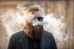 Vapemens Het openluchtportret van een jonge brutale witte kerel met het grote baard laten puft uit stoom van een elektronische si stock afbeelding