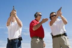 Vapen för instruktörAssisting Men With hand på skjutavstånd royaltyfria bilder