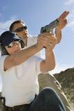 Vapen för instruktörAssisting Woman With hand på skjutavstånd arkivfoton