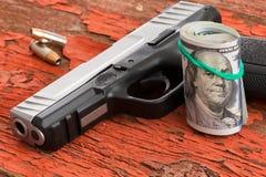 Vapen med en rulle av 100 dollarsedlar Arkivfoto