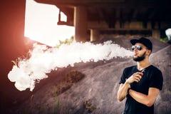 Vaper с бородой в vaping солнечных очков внешний Стоковое фото RF