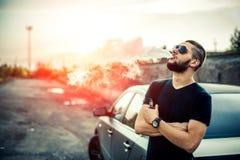 Vaper avec la barbe dans vaping de lunettes de soleil extérieur image libre de droits