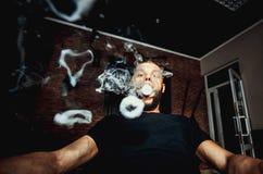 Vaper with beard produce many steam rings. Men with beard vape and produse steam rings royalty free stock image