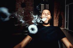 Vaper with beard produce many steam rings. Men with beard vape and produse steam rings stock image