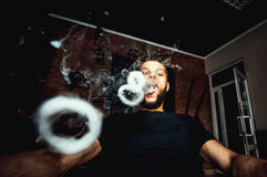 Vaper with beard produce many steam rings. Men with beard vape and produse steam rings royalty free stock photos